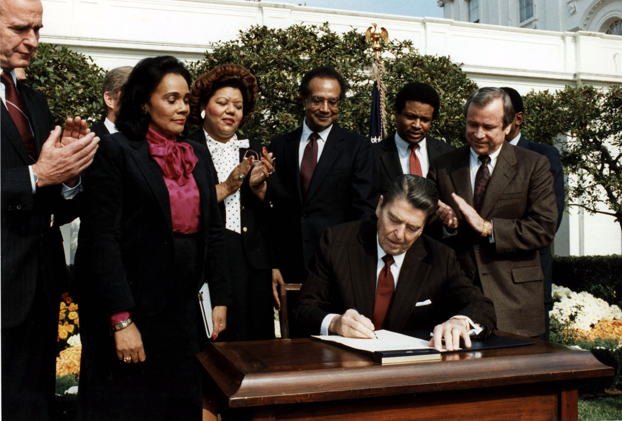 https://upload.wikimedia.org/wikipedia/commons/4/4c/Reagan_signs_Martin_Luther_King_bill.jpg