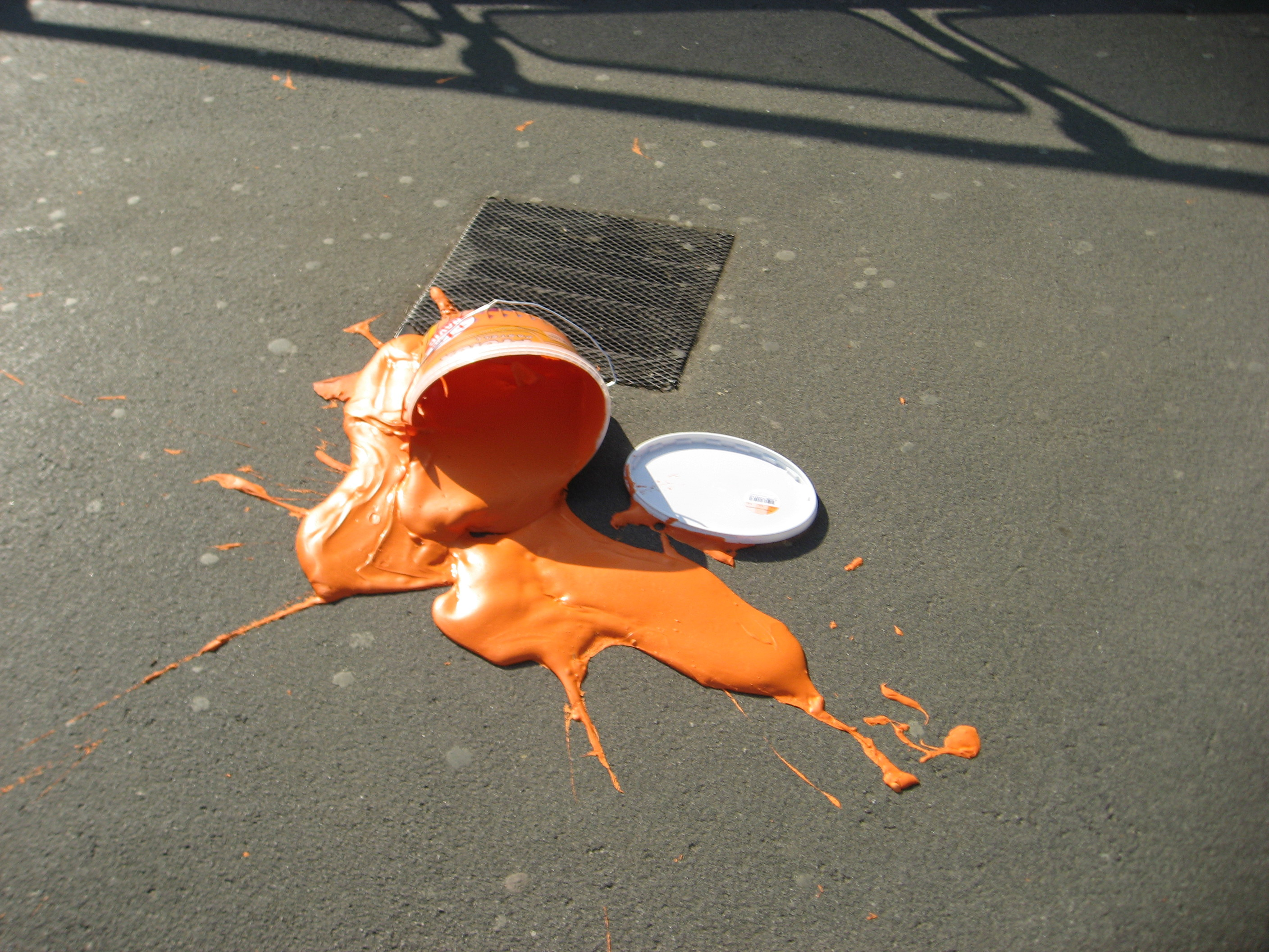 A spilled bucket of orange paint on the pavement