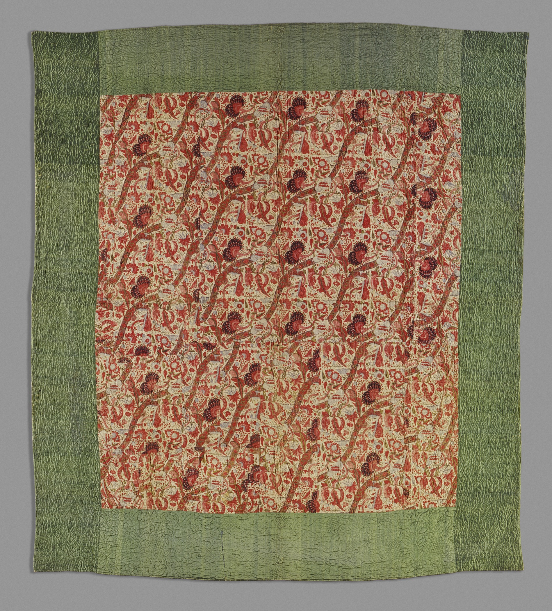 Whole cloth quilt with an orange print and a wide green border