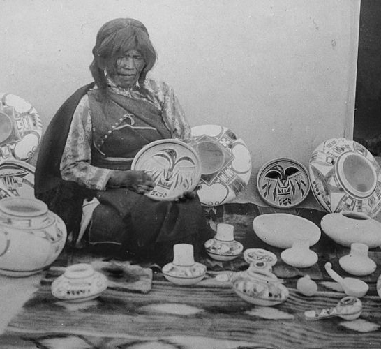 Nampeyo, Hopi pottery maker, seated, with examples of her work, cropped