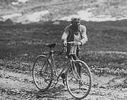 Photographie en noir et blanc d'un cycliste marchant à côté de sa bicyclette dans la montée d'un col.