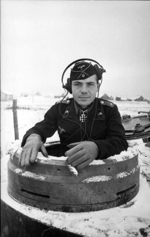alt=A black-and-white photo of a man protruding from the cupola of a tank wearing a black military uniform, side cap and headset.
