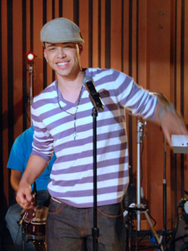 A man looking straight, slightly inclined to the right, wearing a beret, purple shirt with white stripes, a rosary and a pair of jeans, with a microphone in front of him.