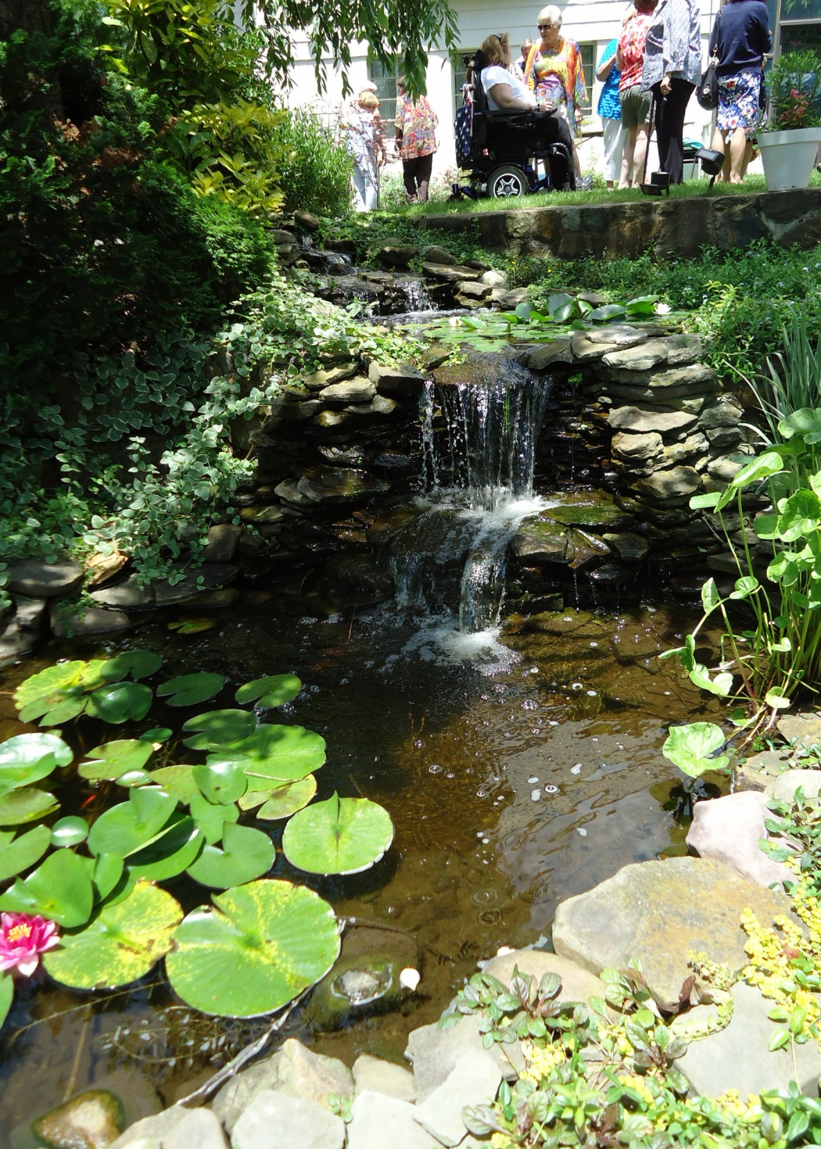 File:Waterfall and pond at a garden party.jpg