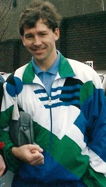 The upper body of a brown haired man. He has a grey bag under his arm, is wearing a blue buttoned-up shirt underneath a white, black, green and blue tracksuit top.