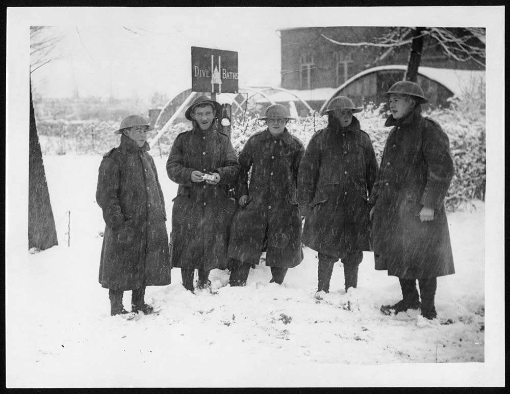 Five British soldiers standing in the snow outside a building with the sign, 'Div[isiona]l Baths' . There appears to be a fairly large town in the background, so these soldiers were probably on a rest period away from the Front.Often men had only two or three baths in a month. Baths were a luxury after life in the trenches. The soldiers were not only dirty and smelly, but usually covered in lice, which were a constant irritation and could carry Trench Fever. [Original reads:  'Snow at the front. Feeling fit after the bath.'] http://digital.nls.uk/74549292
