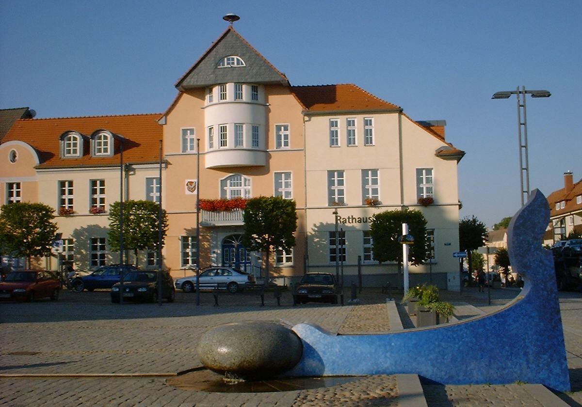 Marktplatz mit Wasserskulptur und Rathaus
