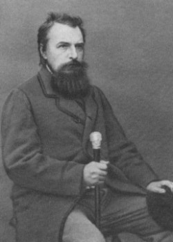 Photo of bearded, seated man holding a cane