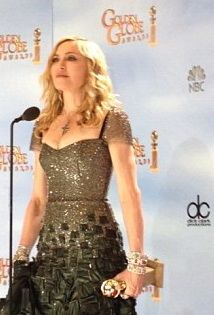Madonna standing in front of a microphone holding an award