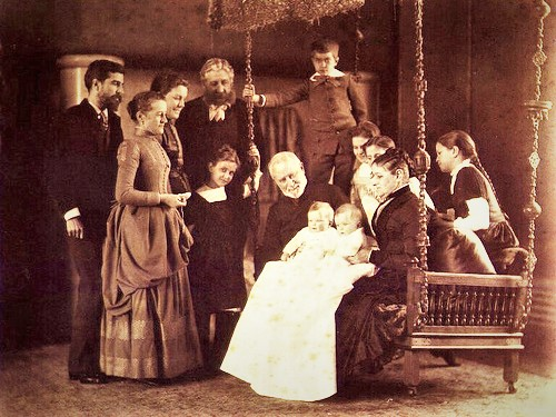 Louis Comfort Tiffany (far left) with his parents (seated), pictured holding Tiffany's twin daughters Louise and Julia Portrait Louis Comfort Tiffany with his parents and his children 1888.jpg