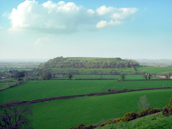 An aerial view over green fields and hedgerows toward a large conical hill