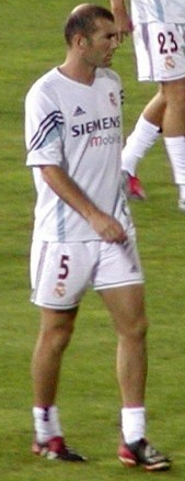 "A dark-haired man wearing a white shirt and white shorts with the number ""5"" displayed on the lower right thigh."