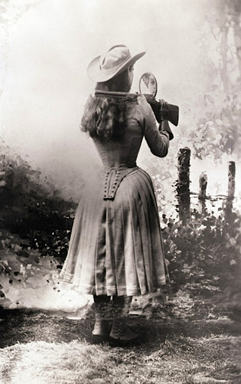 Annie Oakley shooting over her shoulder using a hand mirror. Annie Oakley shooting over her shoulder using a hand mirror..jpg