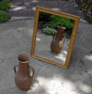 A mirror, reflecting a vase.