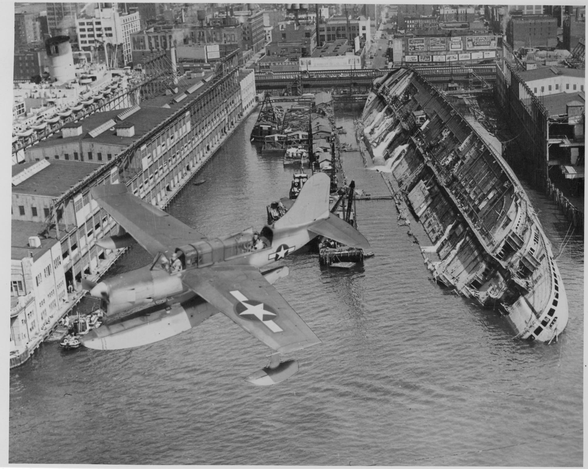 El USS Lafayette (anteriormente SS Normandie), semidesmantelado en 1943 (en primer plano un Curtiss SO3C Seamew de la USAF).