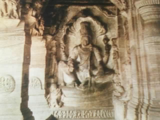 Indoor white relief sculpture of seated deity with 4 arms