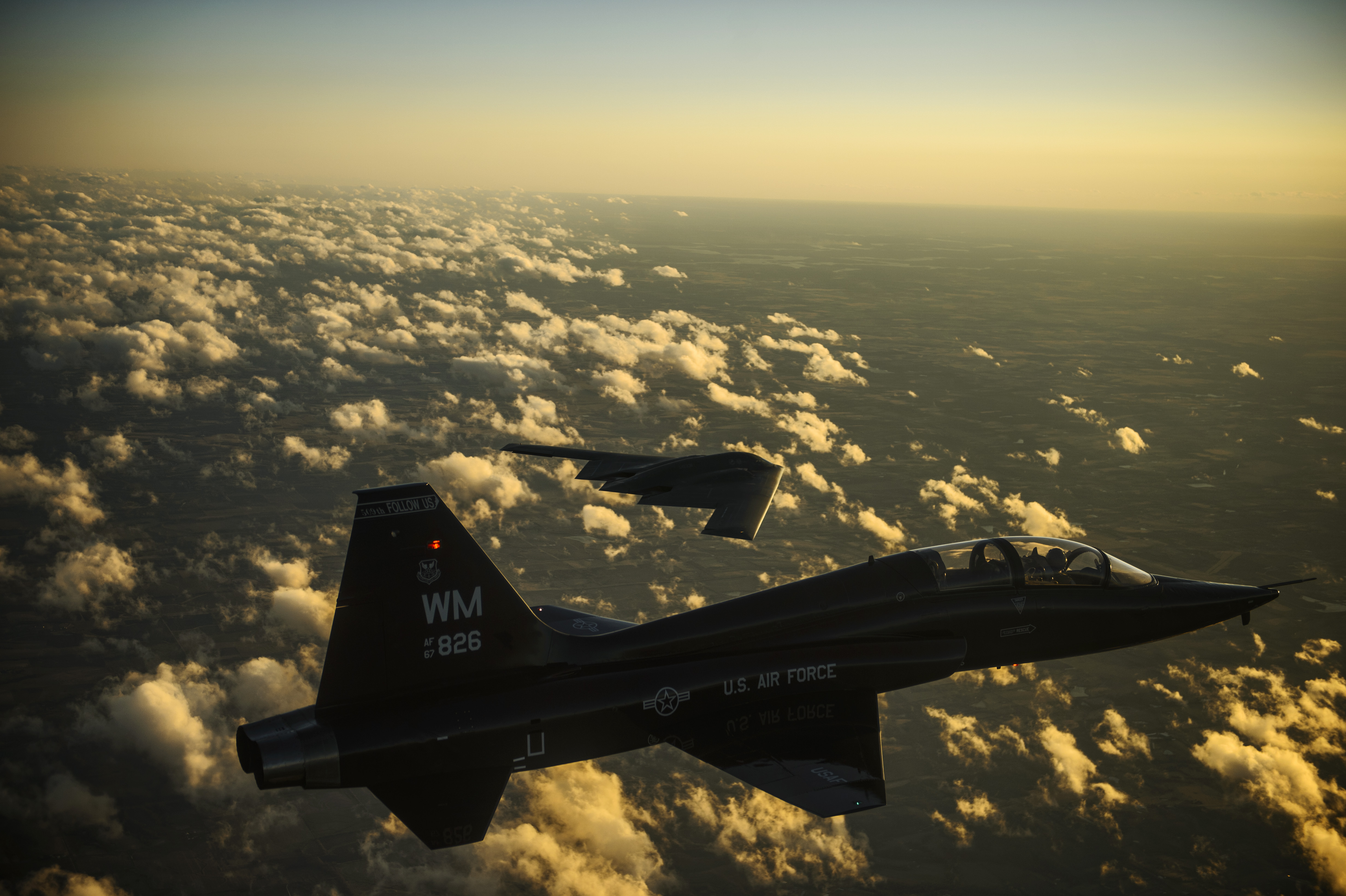 A U.S. Air Force T-38 Talon aircraft and B-2 Spirit aircraft fly in formation during a training mission over Whiteman Air Force Base, Mo., Feb. 20, 2014 140220-F-RH756-606.jpg