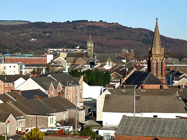 A rooftop view of Neath Two church steeples rise above the roofs of Neath. The nearest is known locally as the 'Penny Brick' church. It was built by public subscription, and a penny donated would pay for one brick. The other church is St Davids.