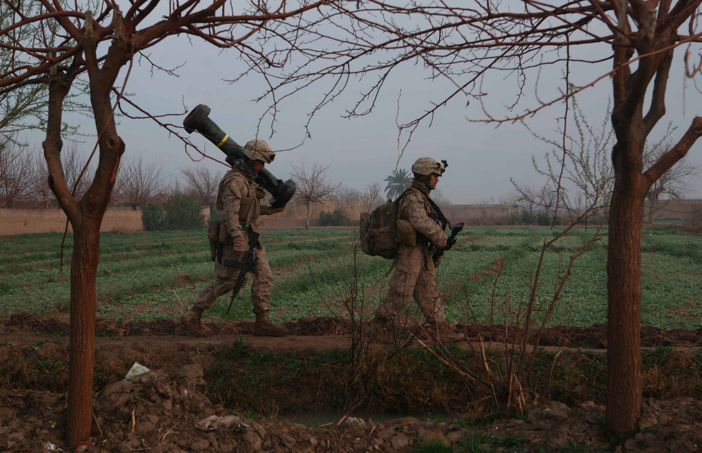 soldiers walk along field with carrying large weapons