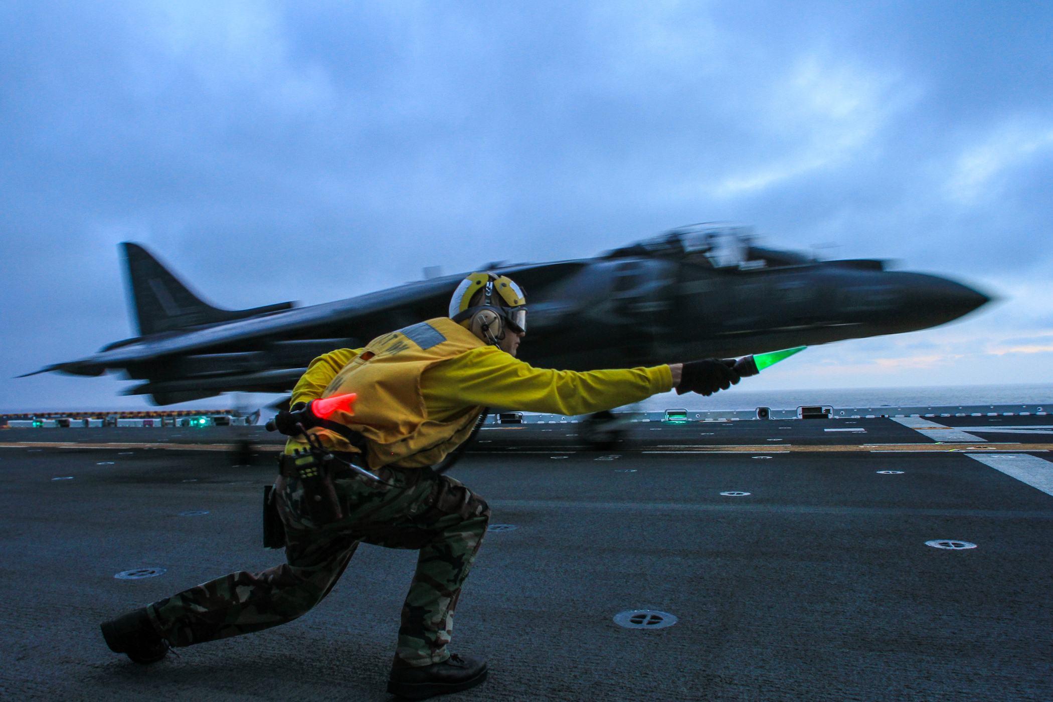 File:A flight deck crewman clears an AV-8B Harrier to take off during