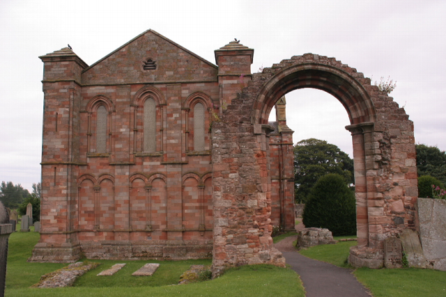 A view Coldingham Priory showing the Choir still standing, with a single arch of the south aisle still standing.