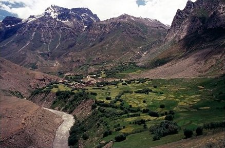 A farmland in Kargil lies straddled below the mountains and above a flowing stream.
