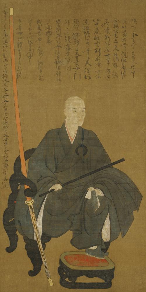 一休宗純像(奈良国立博物館所蔵)1447年(文安4年)一休が54歳の頃の作で、曲彔に座す一休は傍らに「朱鞘の大太刀」を立てる。上部は一休の自賛。Wikipediaより