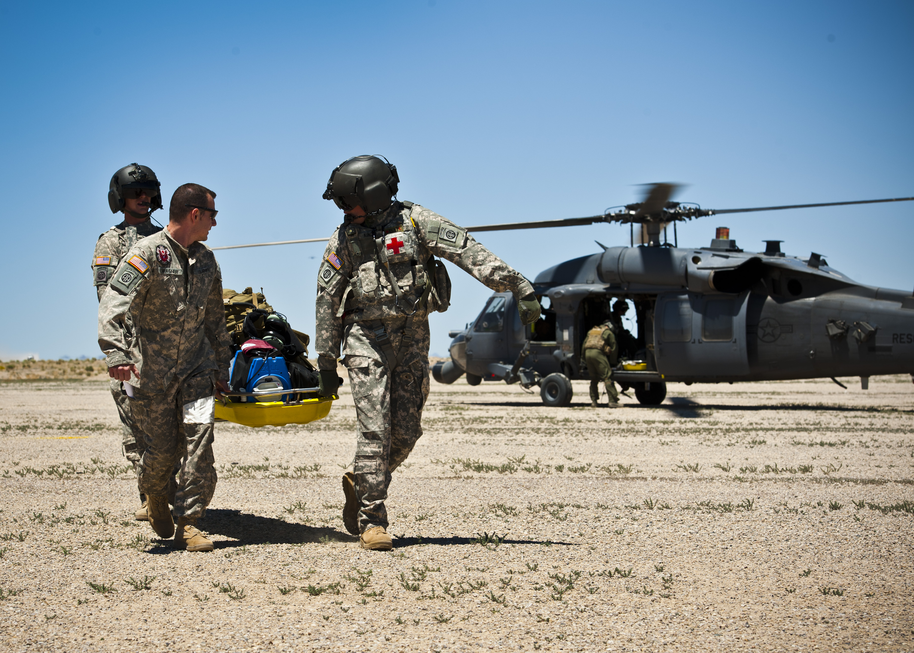 military men carrying a wounded soldier