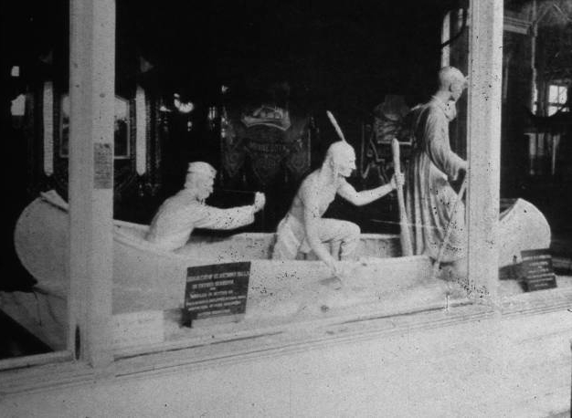 Photograph of an elaborate butter sculpture of a priest sitting in a boat with two guides exiting the boat, one of whom has clear indigenous American garb