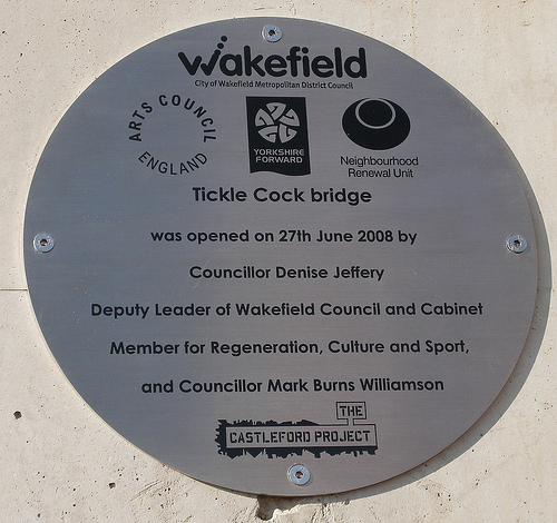 Oval metal plaque fixed to a wall.