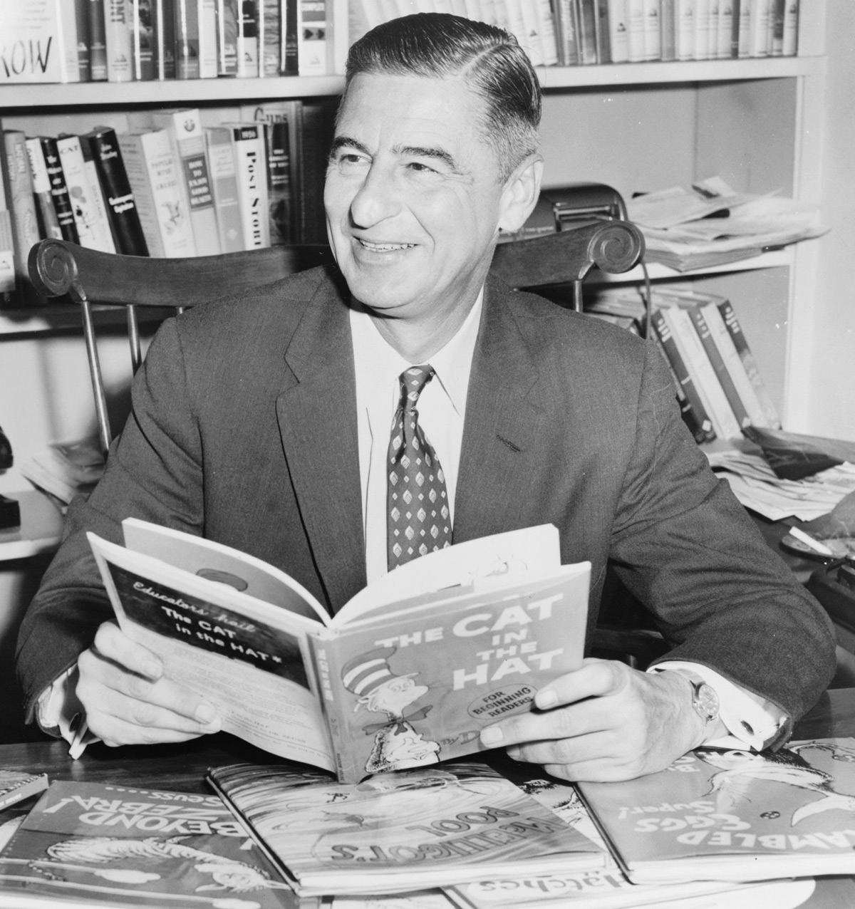 Geisel in 1957, holding ''[[The Cat in the Hat]]'' which inaugurated his [[Beginner Books]]