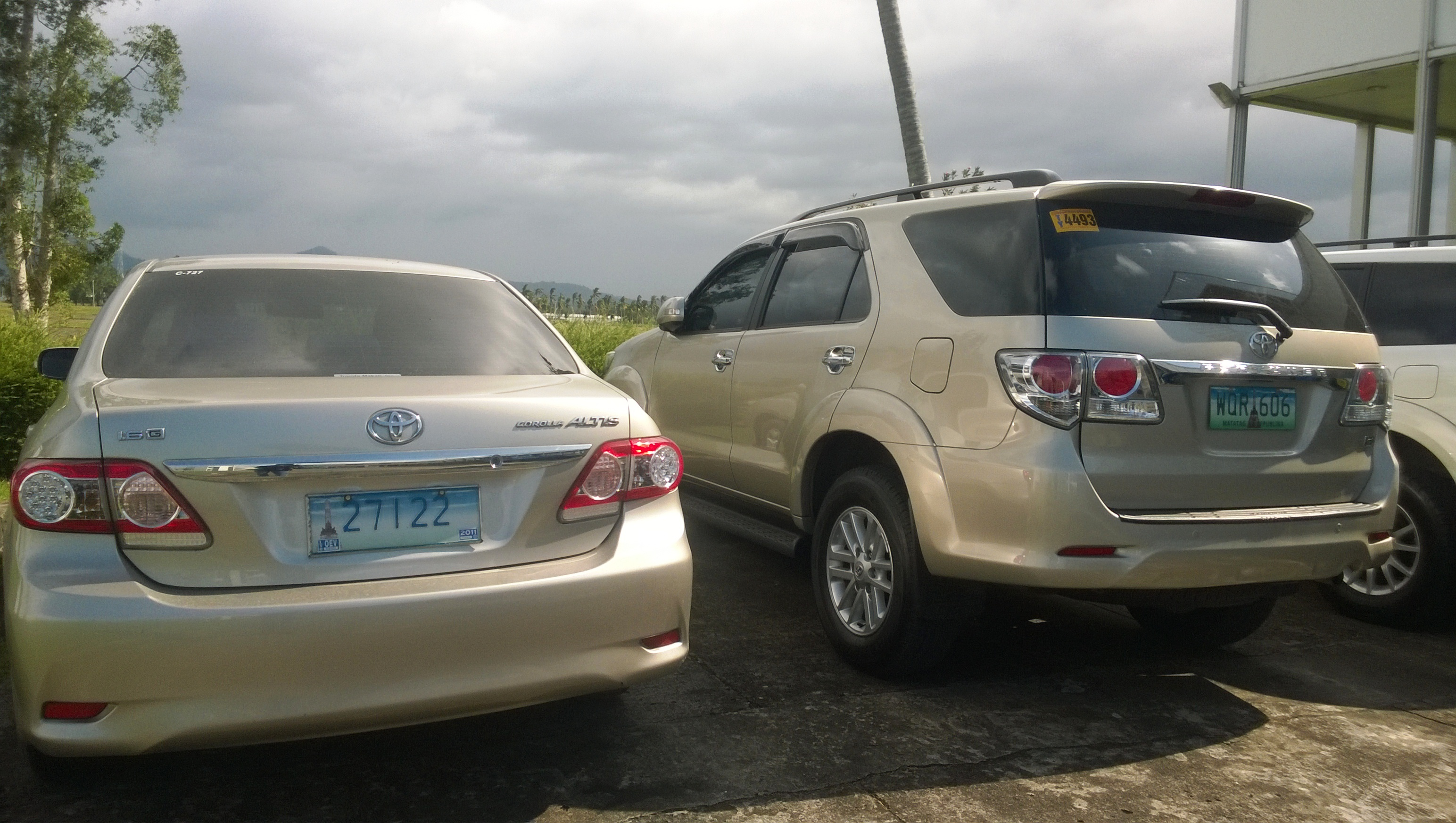A toyota corolla altis with diplomatic oev plates side by side a green plated private toyota fortuner notice the difference in the placement of the