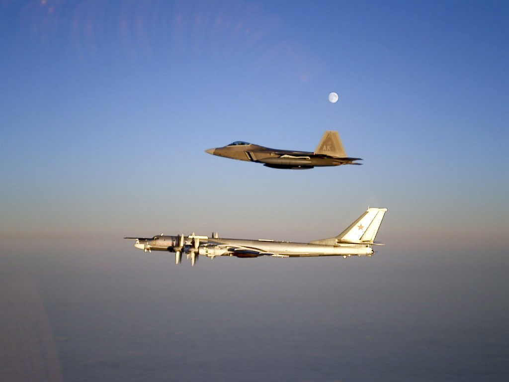 Aerial port view of two aircraft in flight, one on top of the other. The bottom aircraft is a four-engined propeller-driven aircraft, which is escorted by a jet fighter.