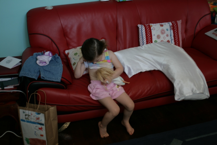 Girl nursing her doll on a red couch.