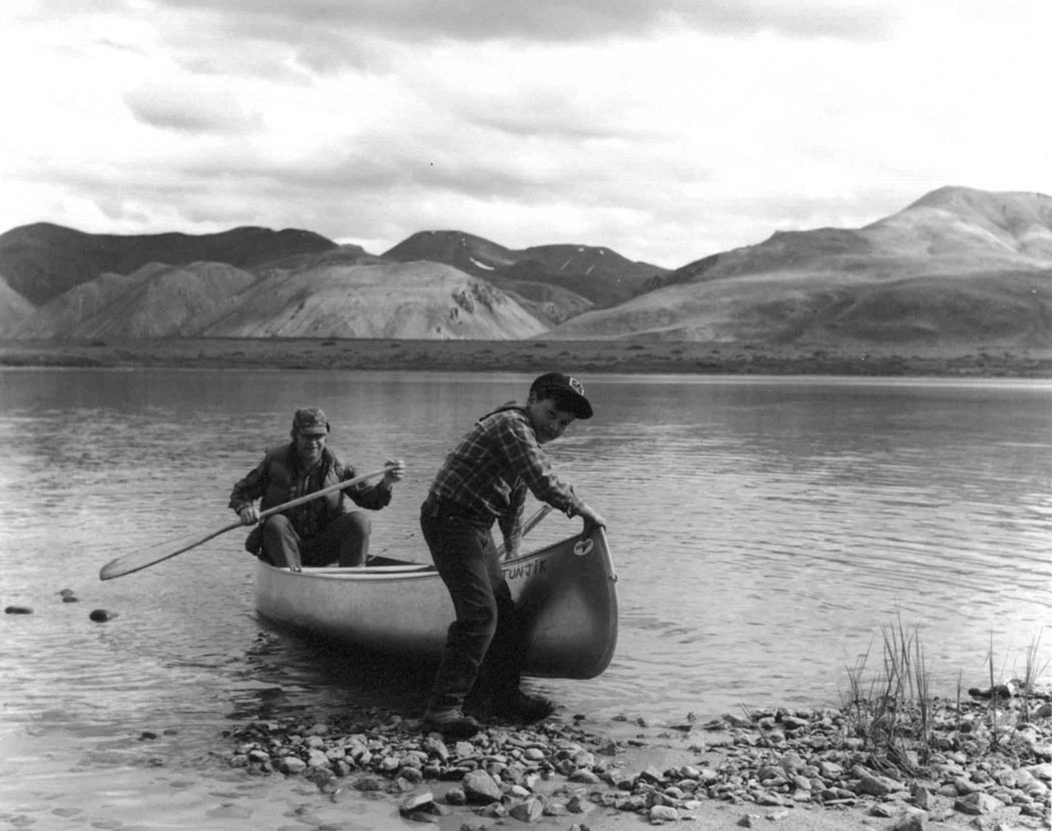 file black and white image of a man and boy coming ashore by canoe
