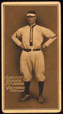 "A baseball card of a man in a light colored baseball uniform with the word ""Vernon"" going down the center stands with his hands on his hips."