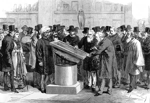 """Lithograph image depicting a group of scholars (mostly male, with the occasional female also in attendance), dressed in Victorian garb, inspecting the Rosetta Stone in a large room with other antiquities visible in the background"""