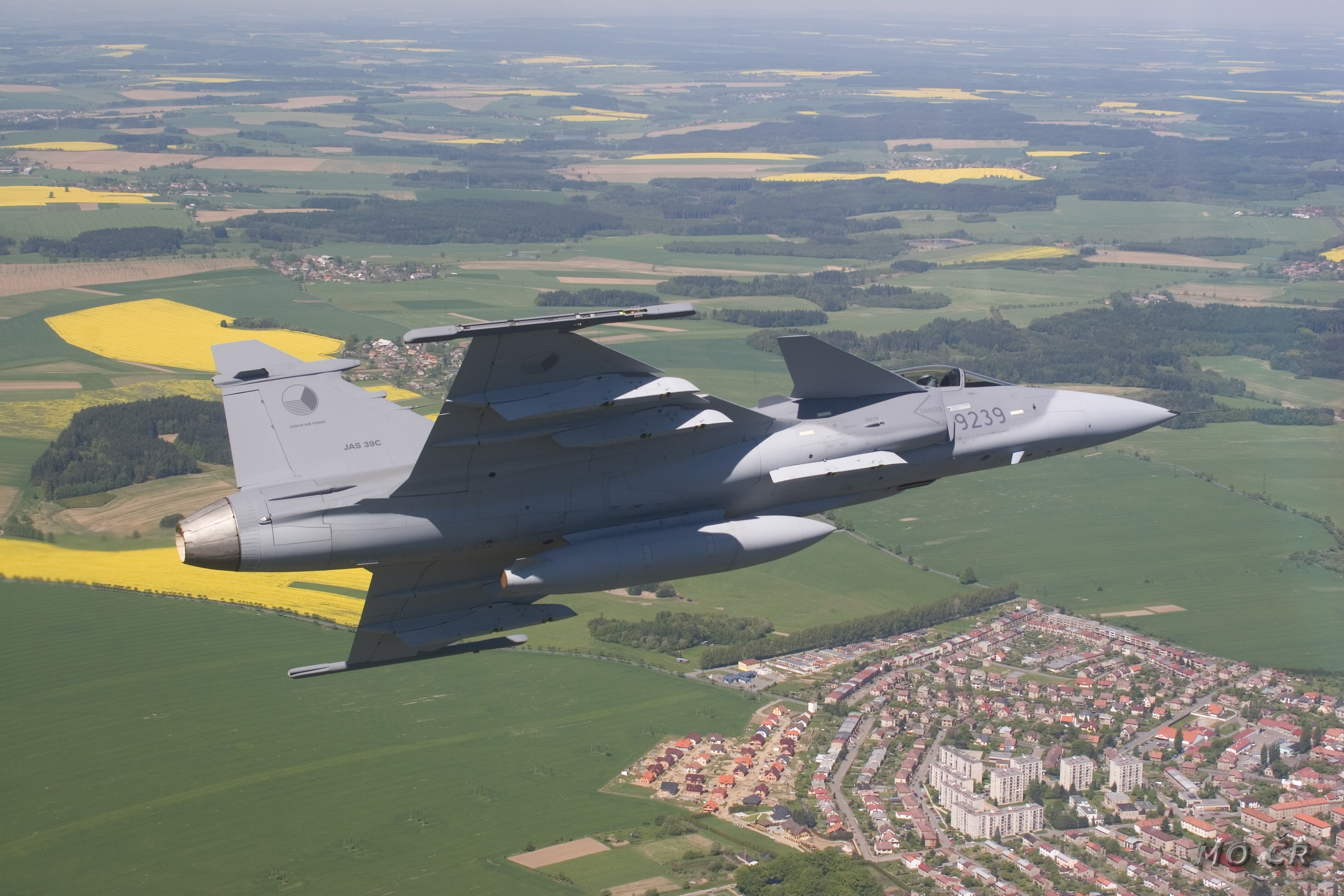 Grey jet aircraft banking right over rural area with residential housing. The background is mostly green with yellow areas.