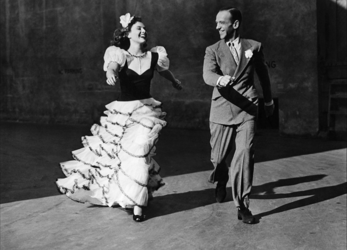 IMAGE Fred Astaire walks with partner in a black & white photo. IMAGE