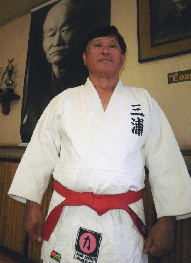 Foto do mestre Miura em sua academia, vestindo kimono branco com a faixa vermelha, tendo como fundo um enorme pôster de Jigoro Kano, o pai do Judô. Iniciando o texto ...