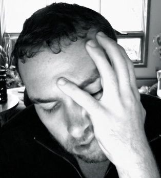 A frustrated and depressed man holds his head in his hand