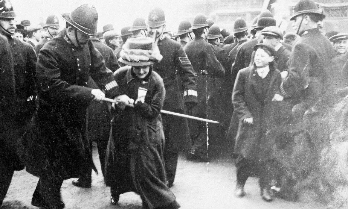 black and white photo of woman holding stick-like object in the centre of a group of uniformed police officers