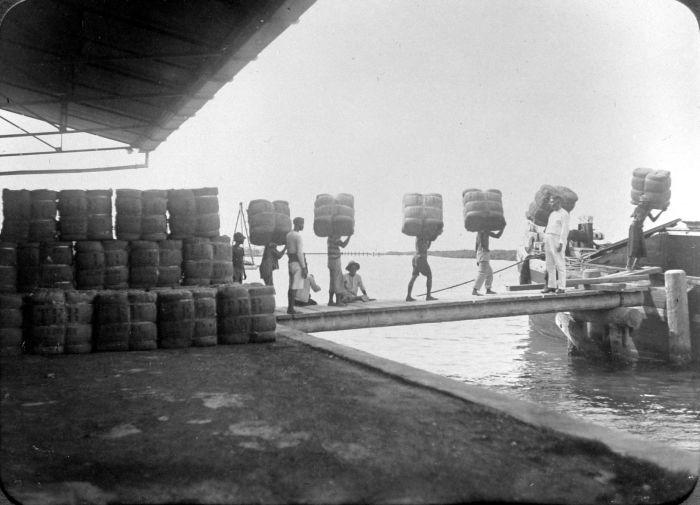 File:COLLECTIE TROPENMUSEUM Mederwerkers dragen balen kapok de lichters in voor transport TMnr 10011380.jpg