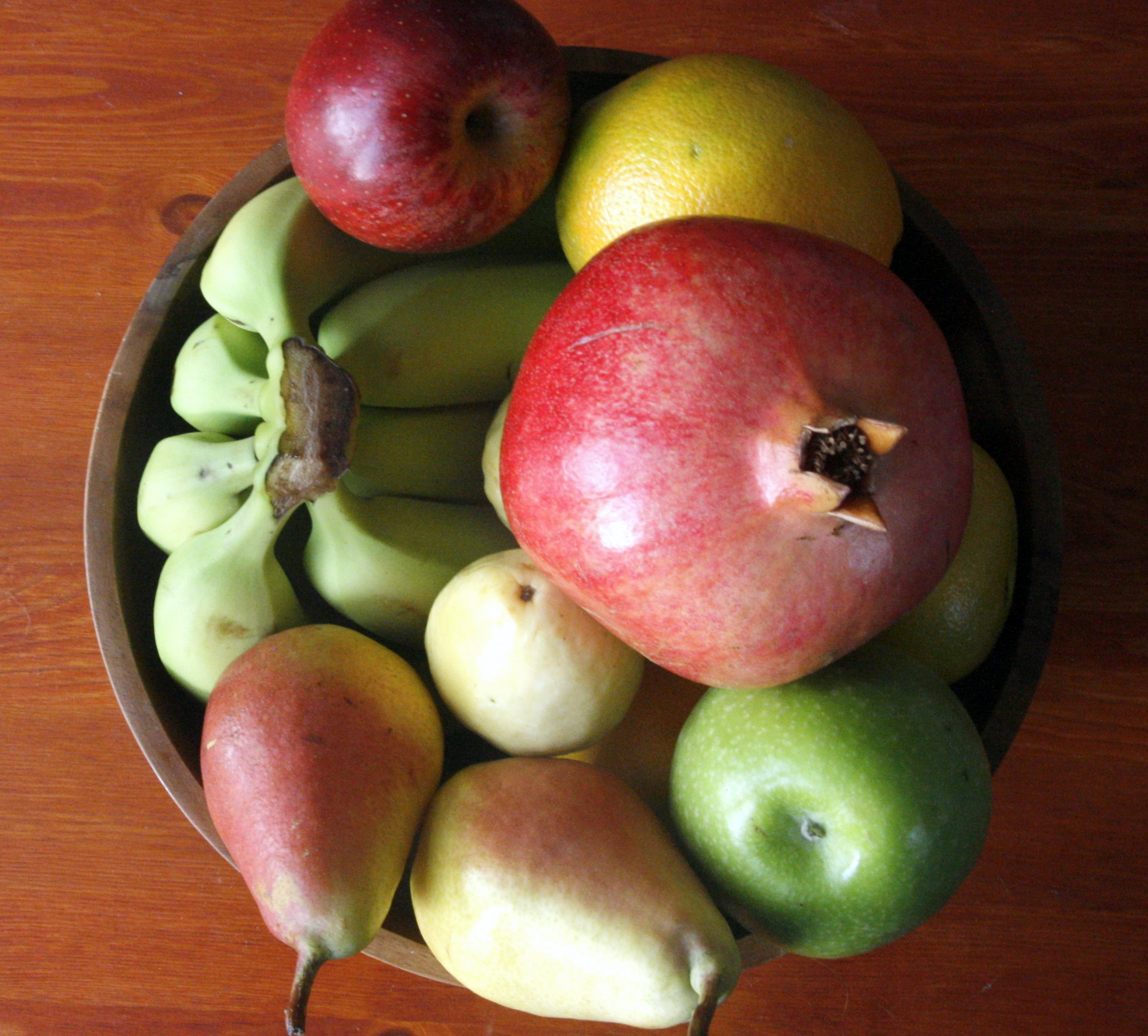 Fruit bowl containing pomegranate, pears, apples, bananas, an orange and a guava