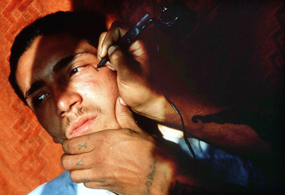 Freshly tattooed teardrops signify his stints in prison for a young member of the 18th Street gang in Los Angeles. Gang tattoo life magazine.jpg