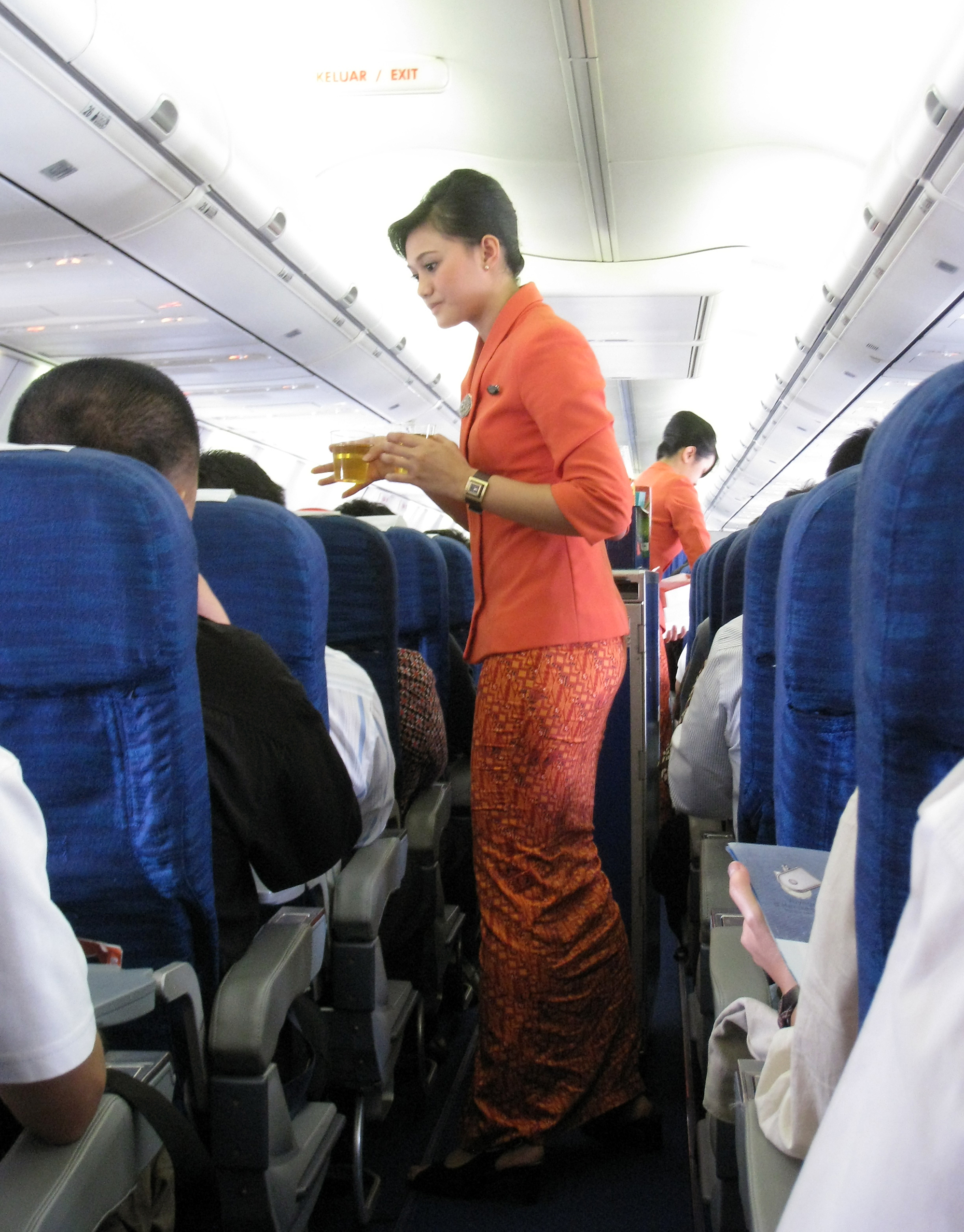 Description Garuda Indonesia Flight Attendants Serving Refreshment.jpg