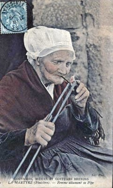 an old photograph of a La Martyre woman smoking a pipe