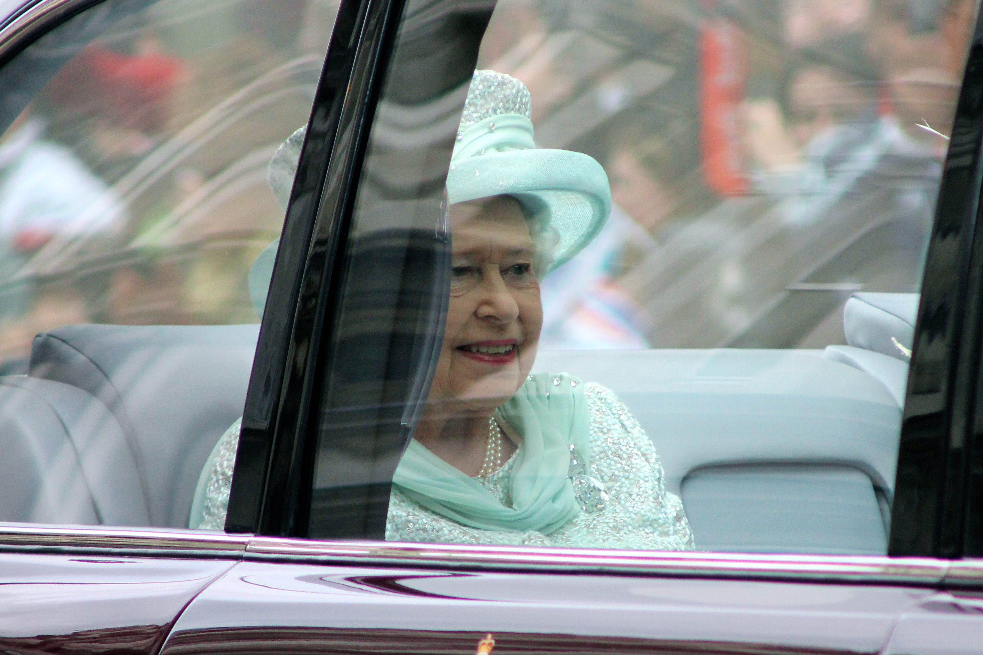 Queen Elizabeth II in her car on a tour.