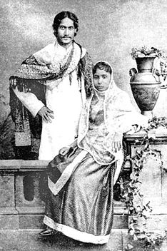 Black-and-white photograph of a finely dressed man and woman: the man, smiling, stands akimbo behind a settle with a shawl draped over his shoulders and in Bengali formal wear. The woman, seated on the settle, is in elaborate Indian dress and shawl; she leans against a carved table supporting a vase and flowing leaves.