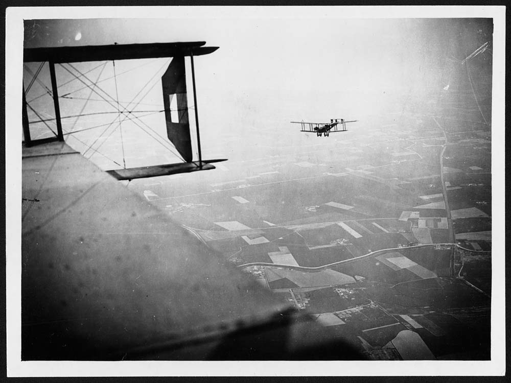 Handley-Page bombers on a mission, Western Front, during World War I. This photograph, which appears to have been taken from the cabin of a Handley-Page bomber, is attributed to Tom Aitken. It shows another Handley-Page bomber setting out on a bombing mission. The model 0/400 bomber, which was introduced in 1918, could carry 2000 lbs (907 kilos) of bombs and could be fitted with four Lewis machine-guns.This photograph, which could have been of use to the enemy, has been censored. The caption has been scored through and 'Stopped'  handwritten in blue pencil on the back. [Original reads: 'OFFICIAL PHOTOGRAPH TAKEN ON THE BRITISH WESTERN FRONT IN FRANCE. Up in the air in a Handley-Page, showing another Handley-Page making for the enemy's lines.'] http://digital.nls.uk/74549118